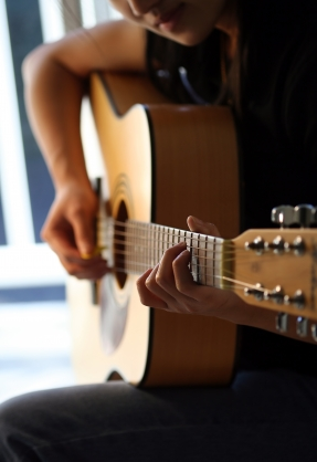 Girl playing the acoustic guitar